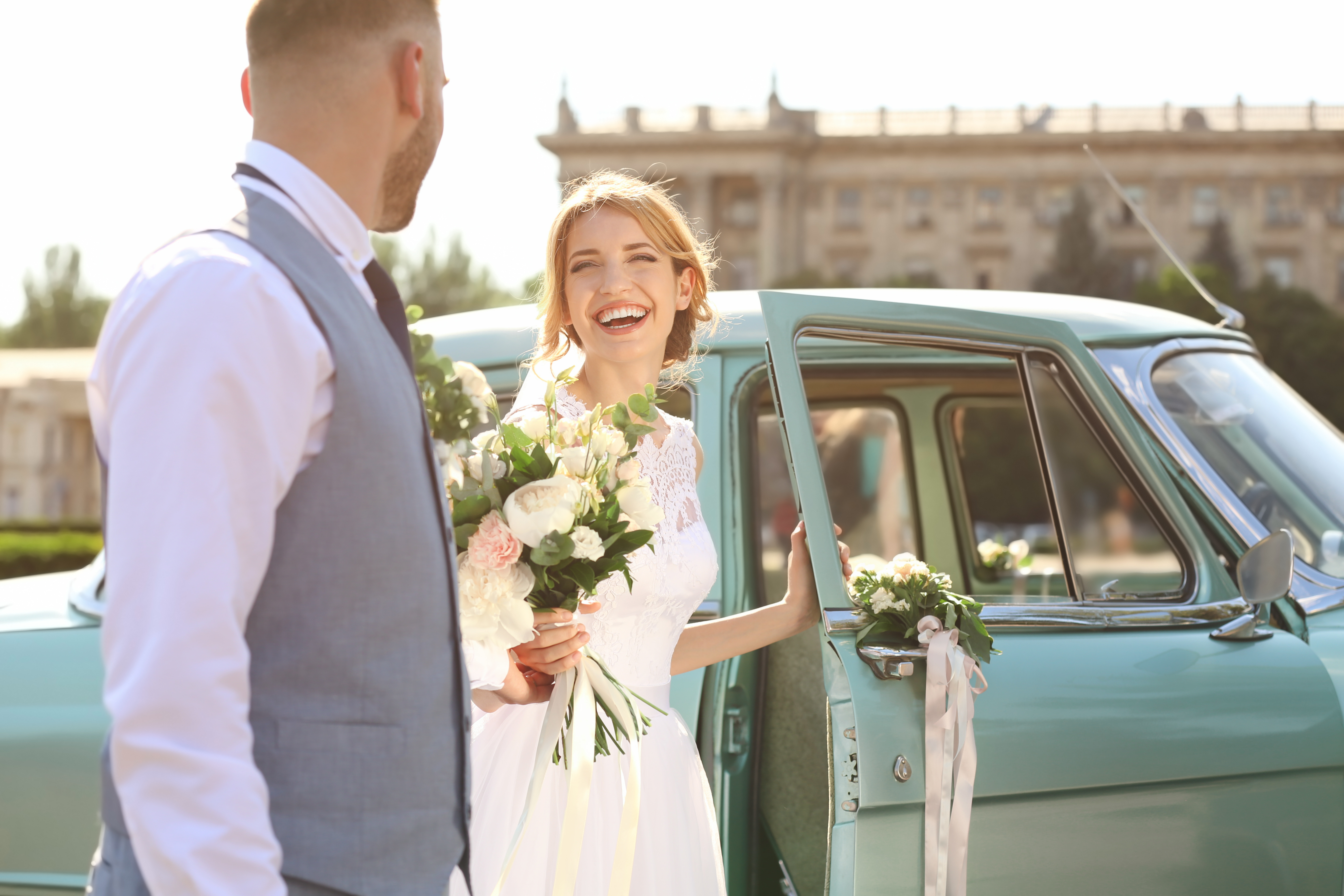 Happy wedding couple near decorated car outdoors